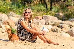 Happy woman sun tanning and relaxing on beach. Stock Photos