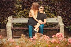 Affectionate couple sitting on bench. Stock Photos
