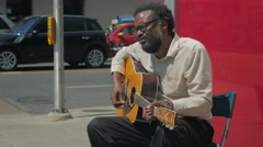 Black Male Street Busking Playing Guitar Pedestrians Walking By Stock Footage