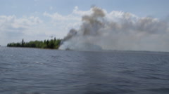 Forest fire on shoreline, helicopter overhead, shot from moving boat Stock Footage