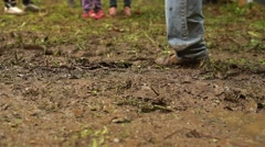 Legs of competitors running through mud on an assault course Stock Footage