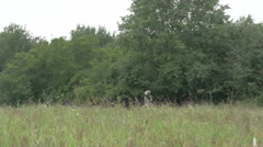 Group of people migrants passing on the edge of the forest, pan right by Sheyno. Stock Footage