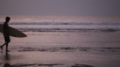 Sunset surfer leaves the water. Stock Footage