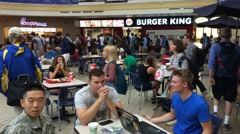 Young students talking while eating at food court in mall Stock Footage