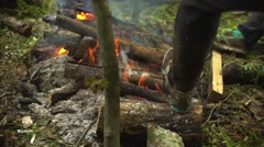 The man in the forest was wet and warm feet in sneakers campfire Stock Footage