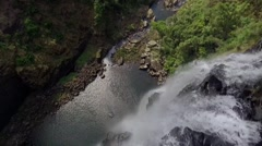 Aerial shot of drone flying off the edge of a waterfall and camera tilting down Stock Footage
