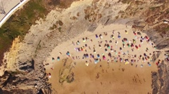 People sunbathing under umbrellas on the beach aerial view Stock Footage