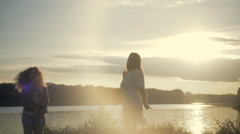 Two European young girls are dancing in bright sunshine. Elegant white dress Stock Footage
