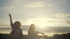 Young girls are having a little party by the lake. Dancing, singing in bright Stock Footage
