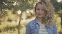 Curly smiling blonde girl standing under the tree in a bright sunshine. Trees on Stock Footage