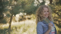 Shy smile of a young blonde girl in front of the camera. Jeans wear. Green Stock Footage
