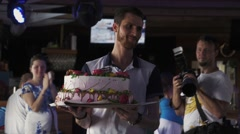 Waiter hold huge cake with flowers in cafe. Celebration. Event. Sweets. Holiday Stock Footage