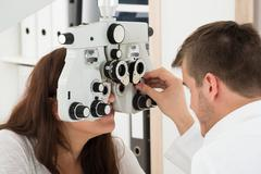A Male Ophthalmologist Adjusting The Panel Of Phoropter While Examining Femal Stock Photos