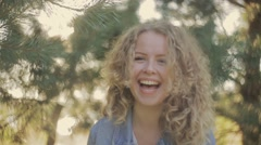 Laughing young lady in a jeans jacket covers her face with her curly hair, then Stock Footage