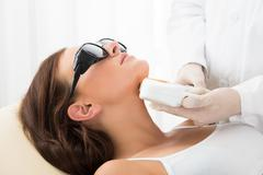Close-up Of A Therapist Giving Laser Epilation Treatment On Women's Neck Stock Photos