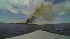 Boat faces smoking shoreline fire Stock Footage