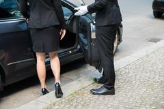 Male Chauffeur Opening The Car Door For The Businesswoman On Street Kuvituskuvat