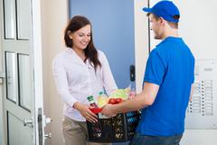 Smiling Young Woman Receiving Groceries From Delivery Man At Home Stock Photos