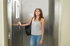 Smiling Young Woman Standing In Elevator And Pressing Button Kuvituskuvat