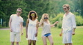 Two young couples in white clothes dancing, enjoying music, having fun outdoors 4k or 4k+ Resolution