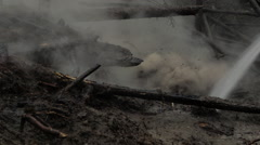 Dirt and mud flung everywhere as burnt fallen trees hosed down Stock Footage