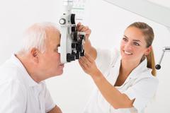 Happy Female Optometrist Doing Sight Testing For Patient In Clinic Stock Photos