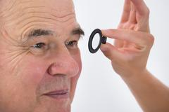 Close-up Of An Optometrist Examining Senior Male Patient's Eyesight With Tria Stock Photos