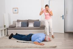 Shocked Young Woman Looking At Her Fainted Disabled Father Lying On Carpet Stock Photos