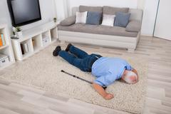 Unconscious Disabled Senior Man Lying On Carpet At Home Stock Photos