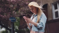 Windy weather in the city. Young woman is using her mobile phone. Cherries Stock Footage