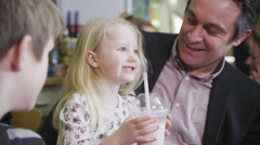 4K Happy family man with cute young children enjoying milkshakes in a cafe Stock Footage