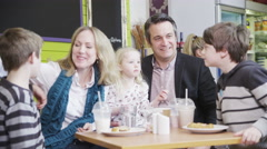 4K Happy affectionate family with cute children enjoying snacks and drinks in Stock Footage
