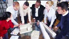 4K Mixed ethnicity team of architects looking at concept models Stock Footage