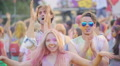Excited friends dancing in crowd of happy young people at Holi color festival Footage