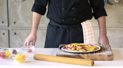 Restaurant hotel private chef preparing pizza adding toppings Stock Footage
