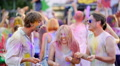 Cheerful young people throwing colorful powder in air, dancing at festival 4k or 4k+ Resolution