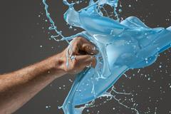 Close-up of a man's fist punching through liquid Stock Photos