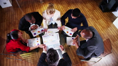 4K View from above of mixed ethnicity business team in a meeting Stock Footage