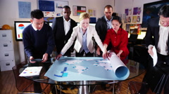 4K Attractive mixed ethnicity business team looking at a map of the world Stock Footage