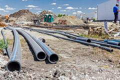 Front view on long black water HDPE pipe with blue stripe at construction sit Stock Photos