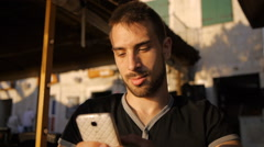Handsome young man texting, browsing internet on mobile phone Stock Footage