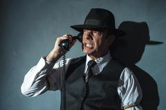 Angry retro film noir man calling with old phone. Stock Photos