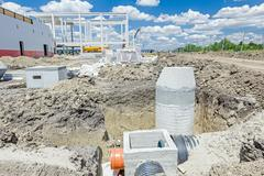 Concrete drainage manhole is unfinished on building site. Stock Photos