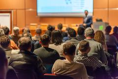 Business speaker giving a talk in conference hall. Stock Photos