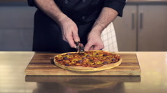 Chef cutting traditonial pizza up into slices Stock Footage