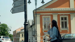Girl eatin ice creams and looking on the signs which show streets Stock Footage