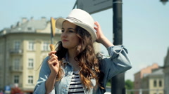 Pretty girl eating ice creams and smiling to the camera in the city Stock Footage