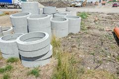 Concrete drainage pipes are on a construction site ready to be placed in. Stock Photos