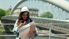 Girl talking on loudspeaker and reading map next to the bridge Stock Footage