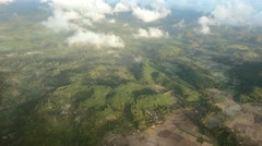 Lombok hills with farming fields and clouds, aerial view Stock Footage